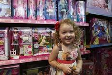 <p>A girl poses near Barbie dolls at a toy store in a file photo. REUTERS/Ali Jarekji</p>