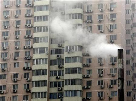 A chimney stack billows smoke in front of an apartment block covered with air-conditioning units in central Beijing November 25, 2009. REUTERS/David Gray