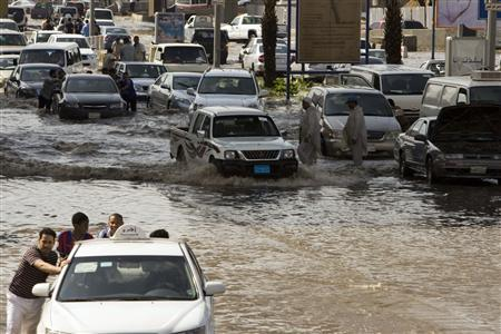 Men push their cars through flooded streets after a storm produced heavy rain in Jeddah November 25, 2009. REUTERS/Caren Firouz