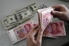 <p>Сотрудник меняет доллары на юани в отделении Bank of China провинции Шаньси 16 ноября 2009 года. Китай отклонил очередные призывы мирового сообщества допустить укрепление юаня, заявив, что оно может подорвать рост местного ВВП и угрожать возрождению мировой экономики. REUTERS/Stringer</p>