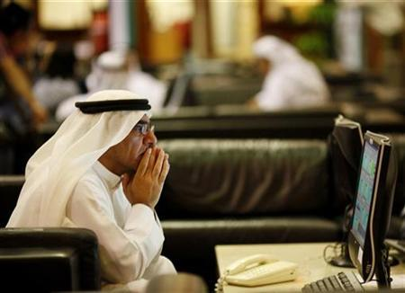 An investor looks at stock exchange information at the Dubai Financial Market, November 30, 2009. REUTERS/Ahmed Jadallah