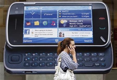 A woman uses her mobile telephone as she passes a Nokia advert in London July 20, 2009. REUTERS/Luke MacGregor
