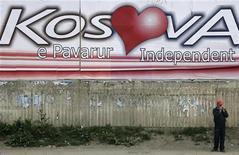 """<p>Косовский албанец стоит напротив гигантского постера """"Независимость Косова"""" в столице Косова Приштина 2 апреля 2008 года. Международный суд ООН начал во вторник слушания, на которых будет рассмотрена законность самопровозглашения независимости Косова в 2008 году. REUTERS/Hazir Reka</p>"""