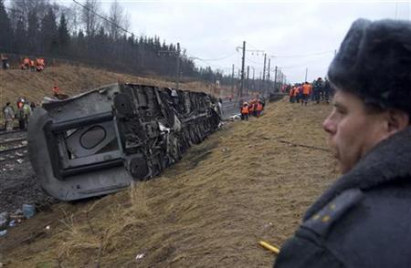 An officer of the Interior Ministry keeps watch at the site of the Nevsky Express train derailment near the village of Uglovka, northwest of Moscow, November 28, 2009. REUTERS/Konstantin Chalabov