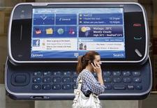 <p>Mulher usa o celular enquanto passa por loja da Nokia, em Londres. A Nokia, maior fabricante de celulares do mundo, informou nesta quarta-feira que espera que o volume do mercado de aparelhos móveis cresça por volta de 10 por cento ano que vem, mais do que analistas esperam.20/07/2009.REUTERS/Luke MacGregor</p>
