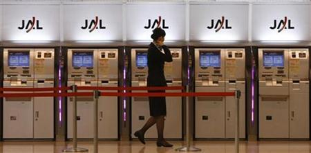 An employee of Japan Airlines walks past its self-ticketing machines at Haneda airport in Tokyo November 13, 2009. REUTERS/Kim Kyung-Hoon