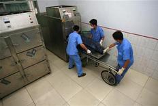 <p>Работники крематория кладут в печь тело человека, погибшего в результате землетрясения в Суйнине, провинция Сычуань, 21 мая 2008 года. Гробы, сделанные из переработанного картона, отказ от использования проникающих в почву бальзамирующих химикатов - в наше время люди все чаще стараются уйти в мир иной при помощи безвредных для природы способов. REUTERS/Stringer</p>