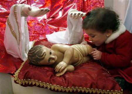 A child touches a statue of Baby Jesus in the Church of the Nativity in the West Bank town of Bethlehem December 25, 2006. REUTERS/Nayef Hashlamoun