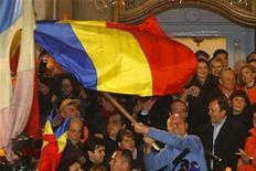 <p>Президент Румынии Траян Бэсеску размахимает национальным флагом после получения первых данных exit polls в Бухаресте 6 декабря 2009 года. Действующий президент Румынии Траян Бэсеску с минимальным преимуществом выиграл второй тур президентских выборов, обойдя кандидата от социал-демократов Мирчу Геоана. REUTERS/Bogdan Cristel</p>