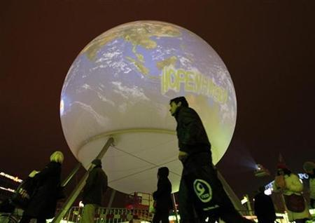 People walk on the street with a huge globe in the background in Copenhagen December 6, 2009. Copenhagen is the host city for the United Nations Climate Change Conference 2009, which lasts from December 7 until December 18. REUTERS/Pawel Kopczynski