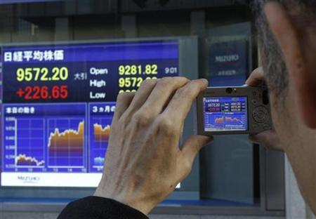 A man takes a picture of a stock index board outside of a brokerage in Tokyo December 1, 2009. REUTERS/Kim Kyung-hoon