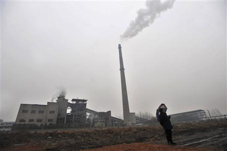 A resident stands near a power plant in Wuhan, Hubei province, December 8, 2009. The largest-ever climate talks formally opened on Monday in Denmark aiming to agree the outlines of global deal to stave off dangerous climate change, such as rising seas and more intense storms. REUTERS/China Daily