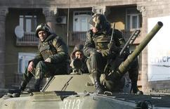 <p>Армянские солдаты сидят на башне бронетраспортера в Ереване 2 марта 2008 года. Армения отправляет в Афганистан 40 военнослужащих на помощь группировке НАТО во главе с Америкой в войне с талибами. REUTERS/David Mdzinarishvili</p>