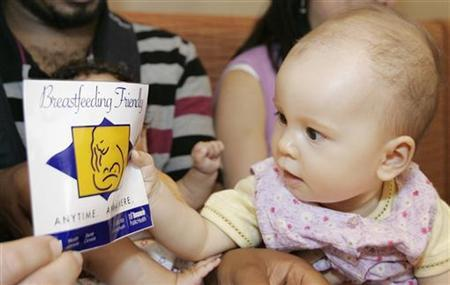 Nine-month-old Elora Yuen holds up a ''Breastfeeding Friendly'' sign at the Commensal Vegetarian Restaurant in Toronto, June 24, 2008. The city of Toronto has distributed 6,100 ''Breastfeeding Anytime Anywhere'' decals that restaurants can display on their door to help nursing mothers identify which restaurants are breastfeeding friendly. REUTERS/Mark Blinch
