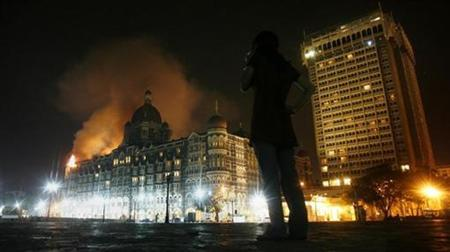 A reporter talks on her phone as smoke is seen coming from Taj Hotel in Mumbai November 27, 2008. REUTERS/Arko Datta