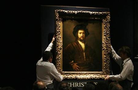Rembrandt's ''Portrait of a man, half-length, with his arms akimbo'' is brought into the auction room by Christie's employees before selling for18 million pounds ($29.59 million) at Christie's auction house in London December 8, 2009. REUTERS/Luke MacGregor