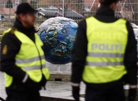 Security personnel stand near a sculpture of a globe outside the United Nations Climate Change Conference 2009 in Copenhagen December 10, 2009. REUTERS/Christian Charisius