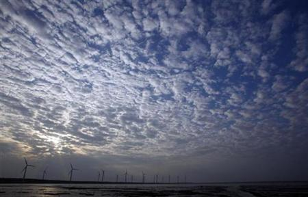 The sun sets behind electricity generating wind turbines in Gaomei Wetland in Taichung December 6, 2009. REUTERS/Nicky Loh
