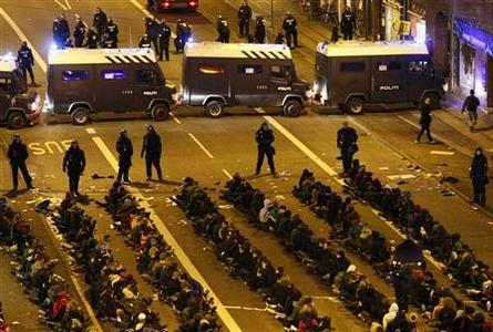 Arrested demonstrators sit on the ground as they are surrounded by police during a rally outside the U.N. Climate Change Conference in Copenhagen December 12, 2009. REUTERS/Christian Charisius