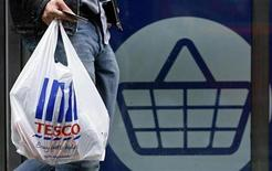 <p>A man carries a carrier bag as he leaves a Tesco supermarket in London October 5, 2009. REUTERS/Luke MacGregor</p>