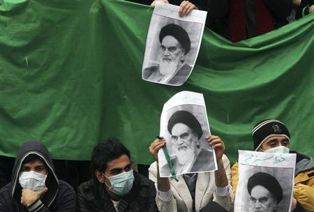 Masked Iranian students, supporters of opposition leader Mirhossein Mousavi, hold pictures of the Islamic revolution's father, Ayatollah Ruhollah Khomeini, during a rally in central Tehran December 13, 2009. REUTERS/via Your View