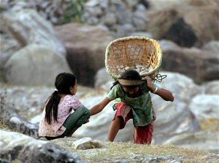 Bhutanese refugee children carry stones in the Timai refugee camp in eastern Nepal March 6, 2005. REUTERS/Desmond Boylan