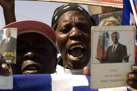 Haitians shout slogans in support of exiled former President Jean-Bertrand Aristide in Port-au-Prince March 9, 2009 file photo. REUTERS/ Kena Betancur