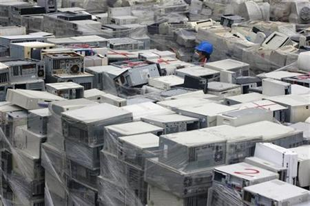 A man walks among piles of discarded computers at one of Taiwan's largest recycling factories in Taoyuan county, northern Taiwan November 24, 2009. REUTERS/Pichi Chuang