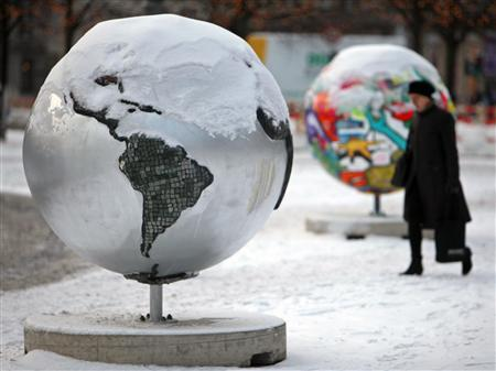 The woman walks by sculptures of globe in Copenhagen December 17, 2009. Copenhagen is the host city for the United Nations Climate Change Conference 2009, which lasts from December 7 until December 18. REUTERS/Pawel Kopczynski