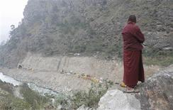 <p>A Buddhist lama stands on a rock as he watches the site of a hydroelectric power plant near River Punatsangchhu in Kamichu in Wangdue district of Bhutan November 17, 2009. REUTERS/Adnan Abidi</p>
