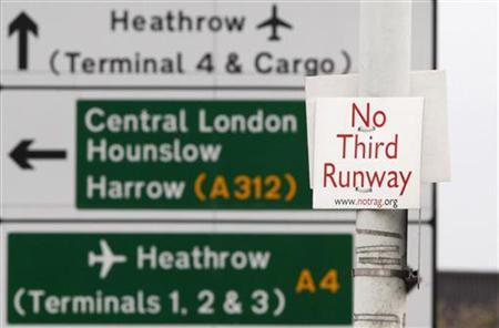 A sign reading No Third Runway is attached to a lampost in front of a road sign for Heathrow Airport at Sipson near London, December 8, 2009. Airports and airlines across Europe moved rapidly to tighten security on U.S.-bound flights on Saturday after a man tried to set off explosives on a plane flying from Amsterdam to Detroit. REUTERS/Luke MacGregor