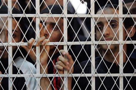 Yemeni al-Qaeda militants listen to a verdict from behind bars at the courtroom of a state security court in Sanaa July 13, 2009. REUTERS/Khaled Abdullah