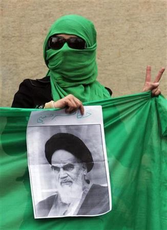 A masked Iranian student, supporter of opposition leader Mirhossein Mousavi, gestures while holding a photo of the Islamic revolution's father, Ayatollah Ruhollah Khomeini, during a rally in central Tehran December 13, 2009. REUTERS/via Your View