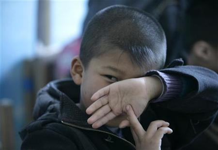 An autistic child looks from behind his hand during a therapy session at the Stars and Rain School for autistic children in Beijing March 23, 2009. REUTERS/Jason Lee