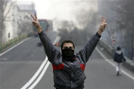 An Iranian protester, with his face covered, flashes victory signs during clashes in central Tehran December 27, 2009. REUTERS/Stringer