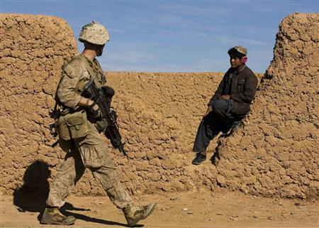 A U.S. Marine from India Company, 3rd Battalion 4th Marines, passes by Afghan boy as he patrols in the small town of Delaram in Helmand province, southern Afghanistan January 6, 2010. REUTERS/Marko Djurica