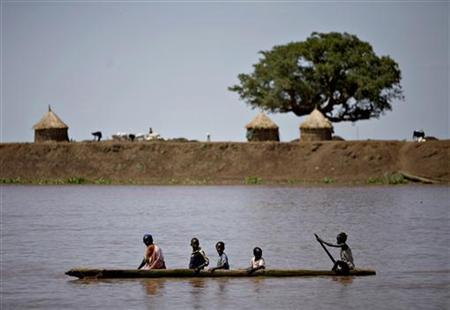 People from the Nuer ethnic group paddle a canoe across a river in the town of Nasir in southeastern Sudan, June 19, 2009. REUTERS/Finbarr O'Reilly