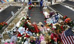 """<p>Rosas e presentes são deixados no túmulo de Elvis Presley durante a comemoração de 75 anos no jardim de Graceland em Memphis, Tenessee, no dia 8 de janeiro. Centenas de fãs desafiaram o frio e a neve para relembrar o """"Rei do Rock"""". REUTERS/Nikki Boertman</p>"""