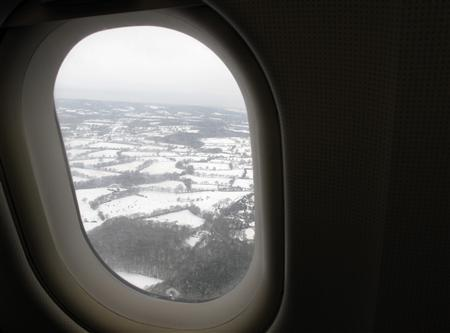 Fields are seen covered in snow through an aircraft window above Gatwick Airport near London January 10, 2010. REUTERS/Stefan Wermuth
