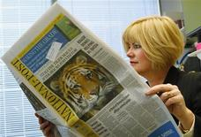 <p>Anne Stone Johnson, Vice President of Weber Shandwick, reads the National Post newspaper in her office in Calgary, Alberta in this October 6, 2009 file photo. REUTERS/Todd Korol</p>