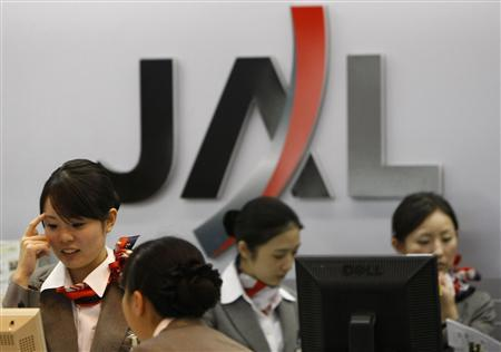 Employees of Japan Airlines (JAL) work in front of its logo at Haneda airport in Tokyo January 10, 2010. REUTERS/Toru Hanai
