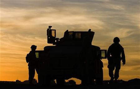 U.S. Marines from 3rd Battalion 4th Marines walk by their vehicle during sunset at base Delaram in Nimroz province, southern Afghanistan January 13, 2010. REUTERS/Marko Djurica