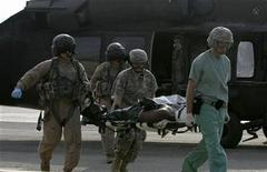 <p>U.S. military medical personnel carry a wounded U.S. soldier on a stretcher after he was evacuated by a helicopter to a U.S. military hospital at the fortified Green Zone in Baghdad October 30, 2006. REUTERS/Thaier al-Sudani</p>