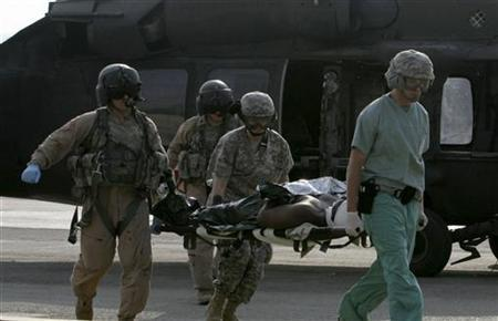 U.S. military medical personnel carry a wounded U.S. soldier on a stretcher after he was evacuated by a helicopter to a U.S. military hospital at the fortified Green Zone in Baghdad October 30, 2006. REUTERS/Thaier al-Sudani