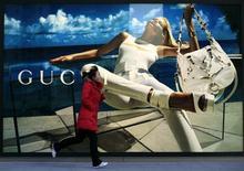 """<p>Una mujer corre frente de un afiche de la firma de alta costura Gucci fuera de un centro comercial en Pekín, 21 ene 2010. China se convertirá en el mayor mercado de lujo del mundo dentro de cinco a siete años, mientras se abre el apetito por las grandes marcas ante el alza de los ingresos de los consumidores, pese a la reciente crisis económica, dijo el jueves un sondeo. Una encuesta del Boston Consulting Group a 2.550 consumidores chinos realizada el año pasado en plena crisis económica global concluyó que los chinos """"aspiran a"""" las marcas de lujo y pueden cada vez más acceder a ellas, dijo el grupo en un comunicado. REUTERS/Jason Lee</p>"""