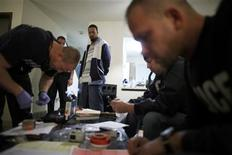 <p>Handcuffed suspect Gerald Ware (C) watches as Kalamazoo police officers catalog evidence in the midst of the execution of a search warrant for marijuana during a raid in search of illegal drugs in Ware's home in Kalamazoo, Michigan, in this November 12, 2009 file picture. REUTERS/John Gress/Files</p>
