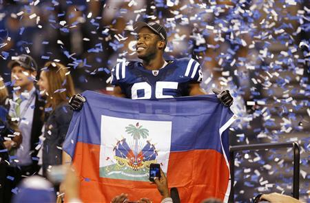 Indianapolis Colts wide receiver Pierre Garcon, whose family is from Haiti, holds the Haitian flag after his team defeated the New York Jets in the NFL AFC Championship football game in Indianapolis, Indiana January 24, 2010. REUTERS/John Sommers II
