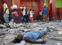 <p>Тело погибшего человека лежит на одной из улиц Порт-о-Пренс, а мимо него проходят мародеры. 21 января 2010 года. Подземные толчки силой 4,7 балла по шкале Рихтера сотрясли Гаити в ночь на понедельник, сообщил Геологический комитет США. REUTERS/Shannon Stapleton</p>