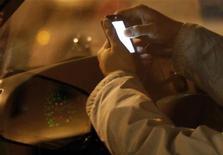 <p>Imagen de archivo en que un conductor revisa su teléfono móvil dentro de su vehículo en Nueva York, 10 dic 2009. El Gobierno de Estados Unidos prohibió el martes que conductores de camiones y buses comerciales grandes envíen mensajes de texto, para evitar el peligro de la distracción mientras conducen estos vehículos. El secretario de Transporte Ray LaHood dijo en un comunicado que la prohibición entrará en vigor de manera inmediata. La norma sigue a una prohibición similar de diciembre para los conductores de vehículos del Gobierno federal. REUTERS/Jessica Rinaldi</p>
