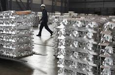 <p>A worker walks between stacks of high purity aluminium ingots at the RUSAL aluminium smelter in the Siberian city of Krasnoyarsk April 4, 2007. REUTERS/Ilya Naymushin</p>